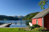 Fjord view over Hardangerfjord with a red boathouse (naust) and a small pier in Ulvik in Hordaland county Norway. poster