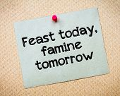 Feast today famine tomorrow Message. Recycled paper note pinned on cork board. Concept Image poster