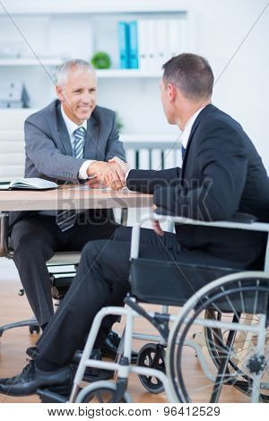 Businessman in wheelchair shaking hands with colleague in the office poster