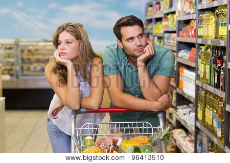Serious bright couple buying food products at supermarket