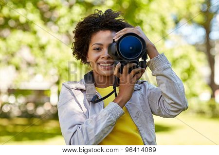 people, photography, technology, leisure and lifestyle - happy young african american female photographer looking to digital camera viewfinder in summer park