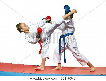 Children with red and blue belts are beating karate blows