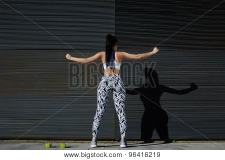Sporty woman with perfect figure and buttocks stretching her arms against wall with copy space