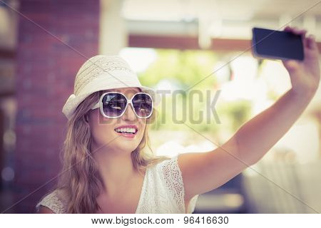 Side view of a pretty hipster woman taking a selfie