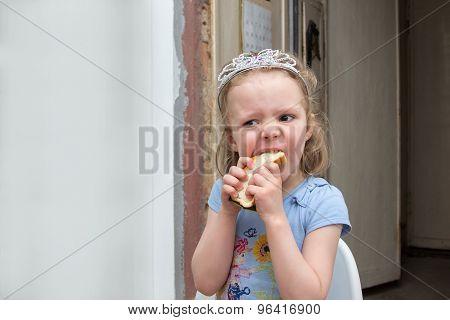 Little Girl In Diadem Hungrily Bites Sandwich