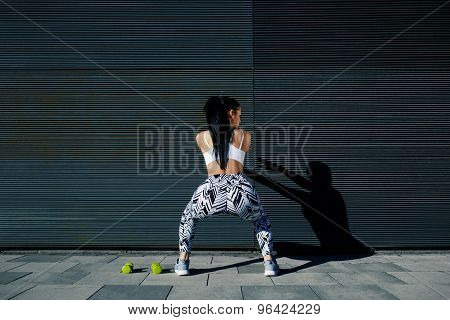 Rear view fit female in sportswear squatting after training on black background outdoors