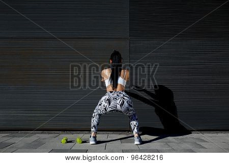 Back view athletic woman with perfect figure and buttocks doing squats against wall with copy space