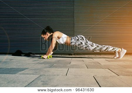 Sporty female in workout gear doing push-ups with some weights against wall with copy space