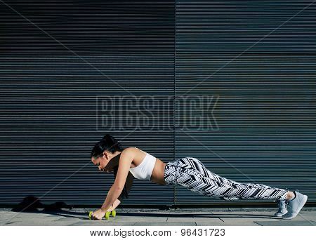 Young woman doing press ups with dumbbells while standing on black background outdoors