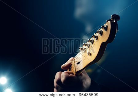 Guitarist on stage - closeup with selective focus on guitar head