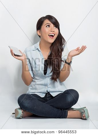 Young Woman Sitting On The Floor While Surprise Looking Up To Copyspace