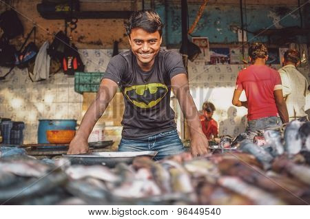 MUMBAI, INDIA - 08 JANUARY 2015: Worker on a fishmarket poses while waiting for customers. Post-processed with grain, texture and colour effect.