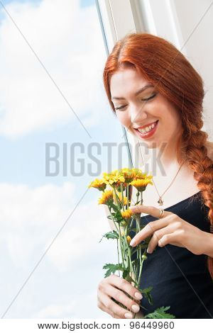 Thoughtful Woman With Flowers Leaning On Window