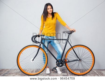 Full length portrait of a happy woman standing near bicycle on gray background. Looking at camera