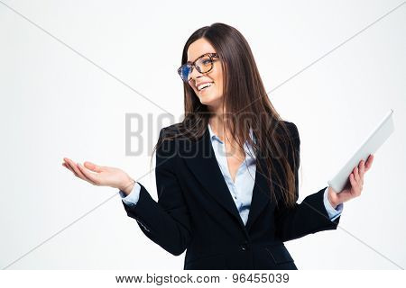 Smiling woman holding tablet computer and shrugging isolated on a white background