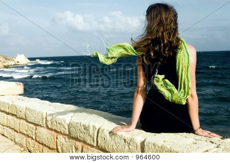 Woman With Shawl, Sitting On Wall An Looking At Sea