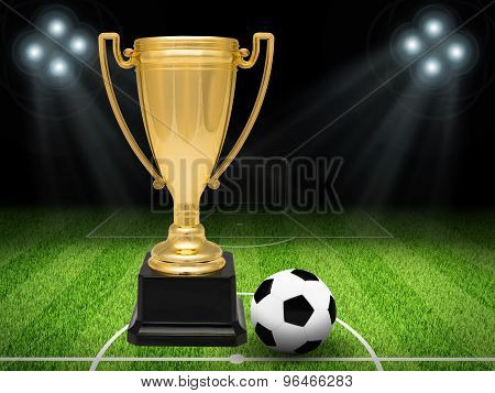 Gold cup with football on pitch