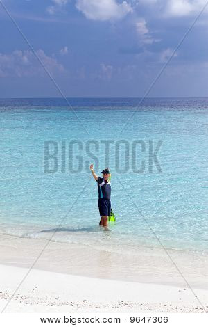 Young sports man with flippers mask and tube at ocean.