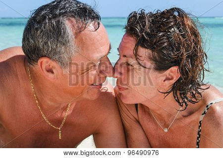 Couple Nose Against Nose, Eye To Eye On The Beach