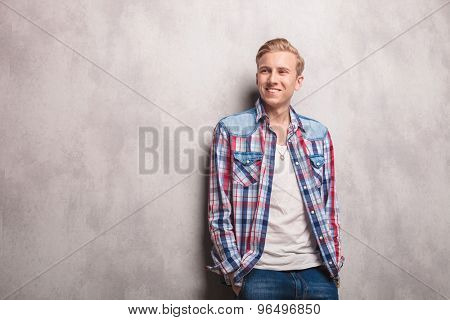 Happy young man smiling away from the camera wile leaning on a wall with his hands in pockets.