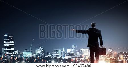 Rear view of businessman against night city gesturing with hand