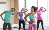 fitness, sport, training, gym and lifestyle concept - group of happy women working out and stretching in gym poster