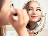 Beauty model teenage girl looking in the mirror and applying mascara make up. Beautiful young woman apply makeup poster