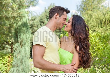 Romantic young couple about to kiss in park