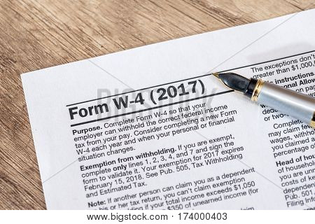 w 4 tax form with pen on desk.