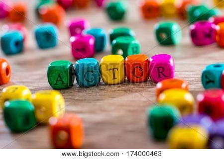 actor - word created with colored wooden cubes on desk.