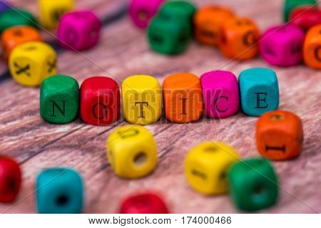 notice - word created with colored wooden cubes on desk. poster
