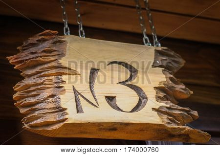 A Wooden Plaque With Number