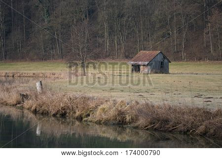 Old cottage by the river and forest