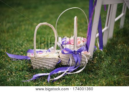 Wedding. Ceremony. On the green lawn is a wicker basket with rose petals for wedding ceremony