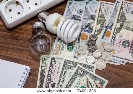 Energy Saving Concept. Electric Light Bulb With Dollar Bills, Pen And Calculator