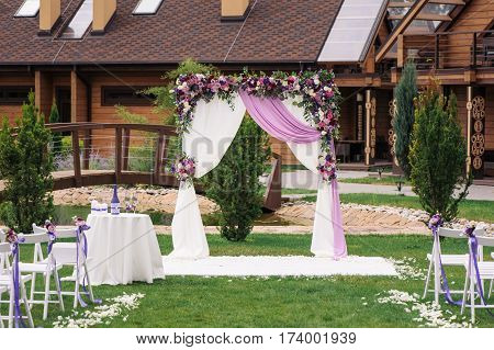 Beautiful wedding arch for marriage decorated with flowers. White decor for bride and groom. Element wedding arches of white and pink roses close-up
