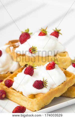 waffles with wild strawberries and whipped cream on white table
