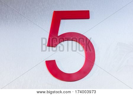 Red number five on a sheet of stainless metal. Position. Serial number. Place in space