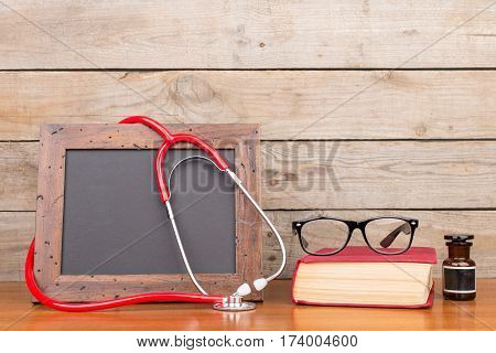 Blank Blackboard, Eyeglasses, Book And Stethoscope On Wooden Background