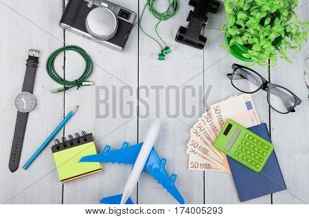 Plane, Passport, Money, Camera, Headphones, Binoculars, Watch, Calculator, Eyeglasses On White Woode
