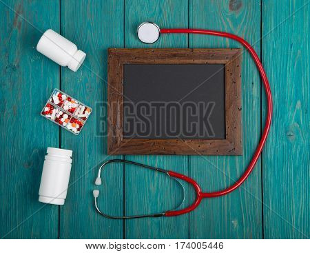 Blank Blackboard, Pills And Stethoscope On Wooden Background