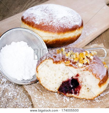 bitten donut with powdered sugar on a wooden table