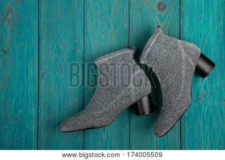 Silvery Fabric Shoes On Blue Wooden Background