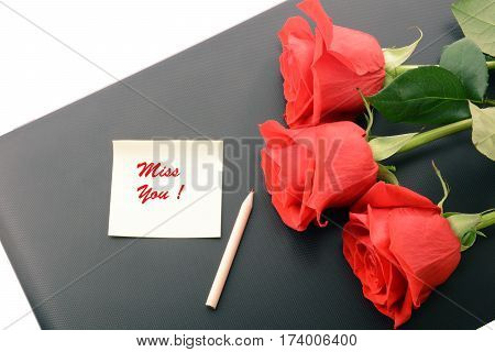 Red roses close up on a laptop isolated on white background. With note and pencil. Miss You