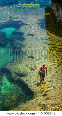 Girl walking in Natural Yellow Pool in Beautiful Cliff Formation, Bizarre Place, Nusa Penida Bali Indonesia.