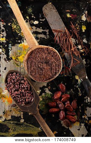 grated chocolate, raw cacao nibs, shredded chocolate and cocoa beans  on vintage painted background