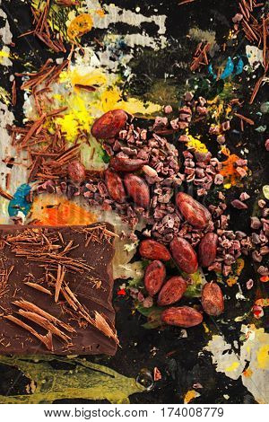 raw cacao nibs, shredded chocolate and cocoa beans  on vintage painted background