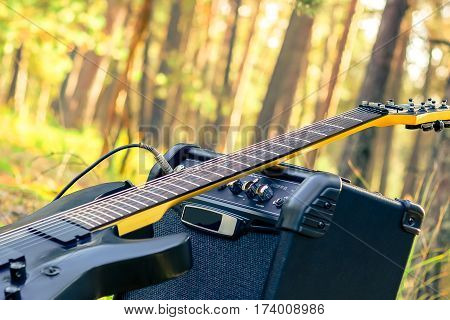 Electric guitar with combo amp in forest. Guit amplifier outdoors