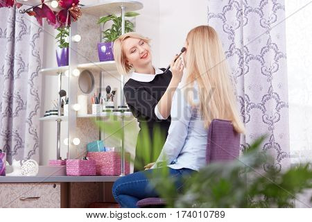 Professional makeup artist using brushes for makeup, painting blush at cheekbones.Wearing black dress making make up of blonde woman with long hair. Beauty salon with stylish interior in violet color