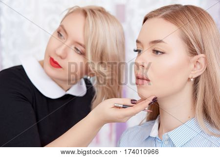 Blonde cosmetologist in black dress and red lips looking at mirror of result of procedure of permanent make up. Make up artist touching face of female clients and showing results for her.